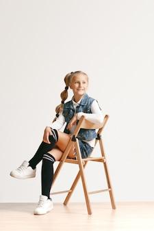 Volledig lengteportret van leuke kleine tiener in het modieuze jeanskleren glimlachen