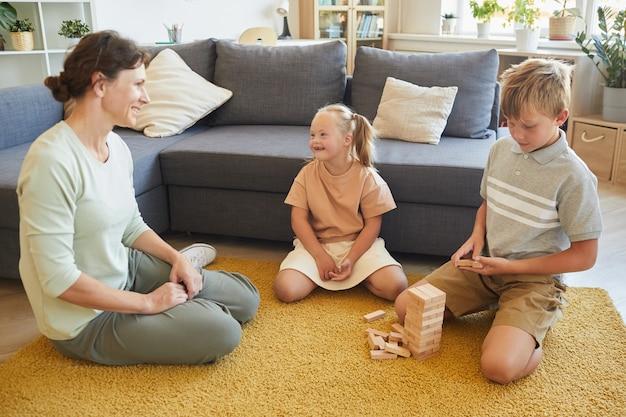 Volledig lengteportret van liefdevolle familie met kind met speciale behoeften bordspellen spelen zittend op de vloer thuis, kopie ruimte