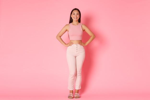 Volledig lengteportret van modieus donkerbruin aziatisch meisje die zich over roze bevinden