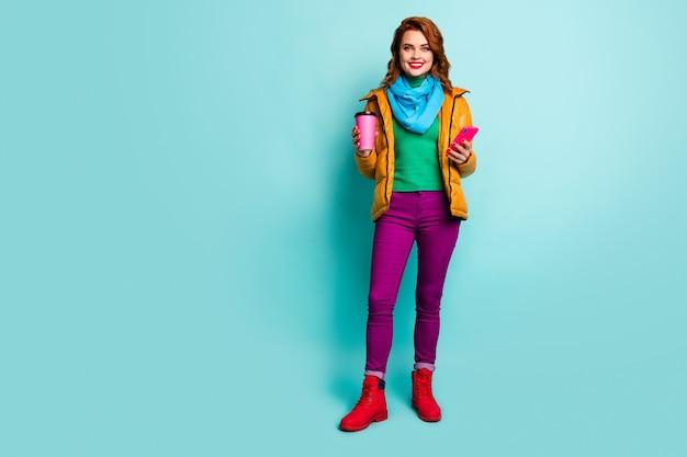 Volledig lengteportret van mooie dame houdt hete koffie drank browsen telefoon lopen straatkleding casual gele overjas sjaal broek trui schoenen.