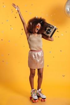 Volledig lengteportret van mooie dolblije vrouw van de afro amerikaanse disco met opgeheven hand, die zich op rolschaatsen bevinden, die boombox houden