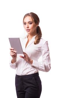 Volledig lengteportret van mooie jonge bedrijfsvrouw die in kostuum een digitale tablet houden en, op grijze muur glimlachen