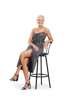 Volledig lengteportret van mooie midden oude vrouw in cocktailkledingzitting op lange stoel