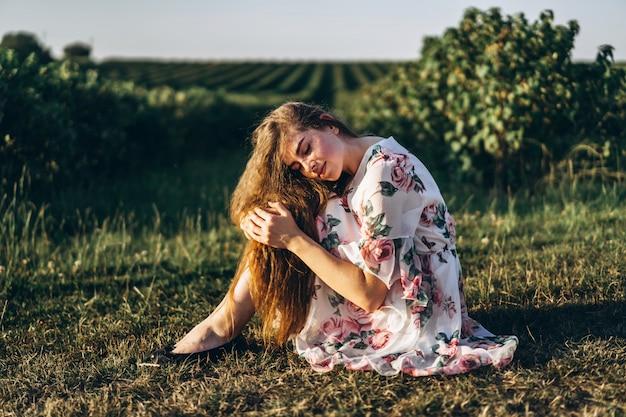 Volledig lengteportret van mooie vrouw met lang krullend haar op besgebied. het meisje in een lichte kleding zit op het gras in zonnige dag