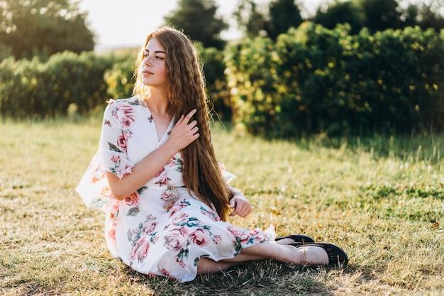 Volledig lengteportret van mooie vrouw met lang krullend haar op besgebied. vrouw in een lichte jurk zit op het gras in zonnige dag