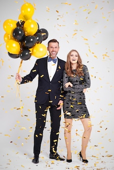 Volledig lengteportret van omhelsd paar met ballon op feestje
