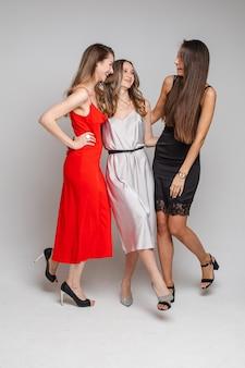 Volledig lengteportret van prachtige dames in rode, zilveren en zwarte cocktailjurken en hakken die allemaal samen lachen op een witte muur in