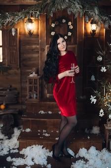 Volledig lengteportret van prachtige donkerharige vrouw in elegante rode jurk en hoge hakken permanent met fluit champagne onder sneeuwval in feestelijk ingerichte kamer met kerstmis
