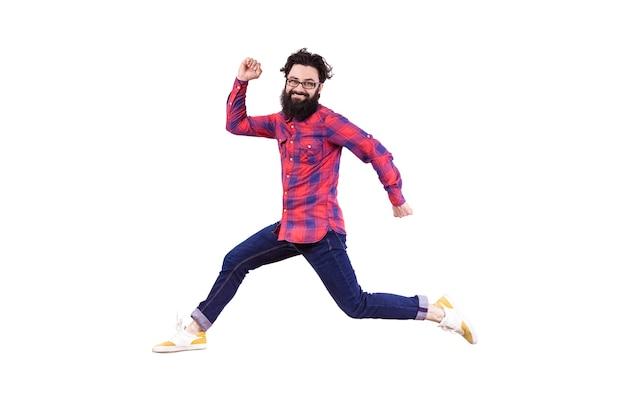 Volledig lengteportret van rennen en springen bebaarde hipster, geïsoleerd op een witte achtergrond