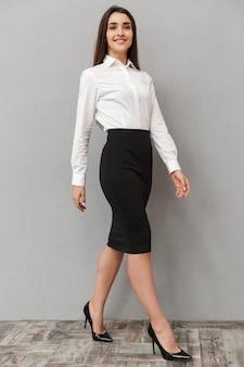 Volledig lengteportret van schattige jonge vrouw 20s met lang bruin haar in wit overhemd en zwarte rok poseren met glimlach, geïsoleerd over witte muur