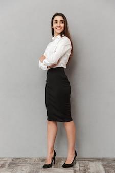 Volledig lengteportret van succesvolle jonge vrouwen20s met lang bruin haar in bedrijfskleding die en gekruiste wapens glimlachen houden, geïsoleerd over witte muur