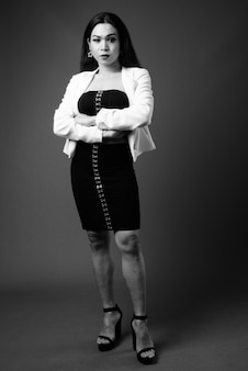 Volledig lengteportret van transgenderonderneemster in zwart-wit