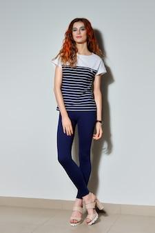 Volledig lengteportret van trendy hipstermeisje met lange benen in strakke blauwe broek, t-shirt met strepen en haarlokken geschilderd in vuurrood.