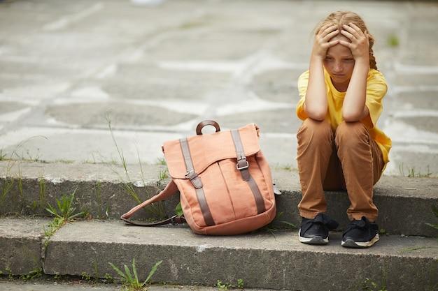 Volledig lengteportret van triest roodharig schoolmeisje zittend op trappen buitenshuis alleen, pesten en outcast concept, kopie ruimte