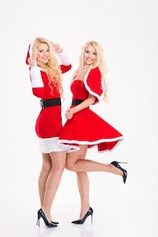 Volledig lengteportret van twee blonde mooie zusterstweelingen in de kostuums van de kerstman die over witte achtergrond wordt geïsoleerd
