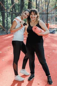 Volledig lengteportret van twee mooie vrouwen die vóór het doen van afvallen oefeningen in een sportpark in de ochtend glimlachen.