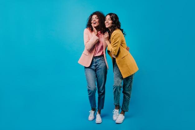 Volledig lengteportret van twee vrouwen die van gesprek genieten