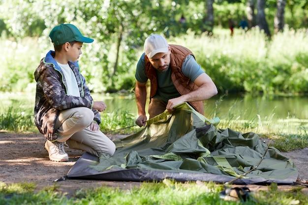 Volledig lengteportret van vader en zoon die tent samen opzetten tijdens het kamperen aan meer in bos, exemplaarruimte