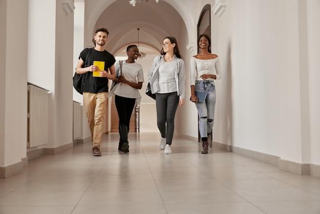 Volledig lengteportret van vier gemengde groep jonge glimlachende mensen, casual gekleed, die door de heldere universiteitsgang lopen. gelukkige aantrekkelijke studenten gaan naar huis na het beëindigen van de lessen.
