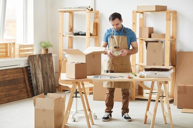 Volledig lengteportret van volwassen bebaarde man die schort draagt die individuele voedselporties verpakt, arbeider in voedselleveringsdienst