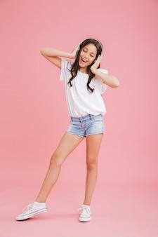 Volledig lengteportret van vrolijk meisje 8-10 in vrijetijdskleding zingend terwijl u aan muziek luistert via draadloze hoofdtelefoons, geïsoleerd over roze achtergrond