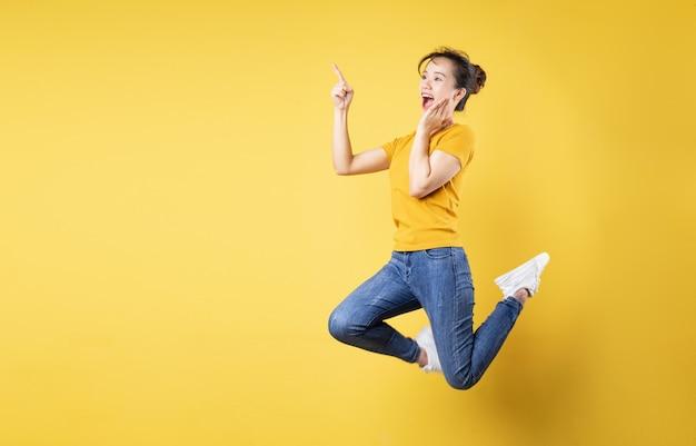 Volledig lengteportret van vrolijk meisje dat omhoog springt geïsoleerd op gele background