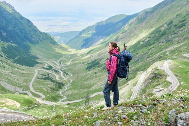 Volledig lengteschot van een vrouw die zich bovenop een heuvel bevindt die tijdens het reizen van het landschap van weg transfagarasan in roemenië geniet