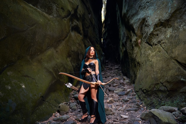 Volledig lengteschot van een vrouwelijke strijder met een boog en pijlen die door het hout wandelen copyspace copyspace boogschieten boogschieten vechter amazon tribal traditionele feminisme macht bekwaam.