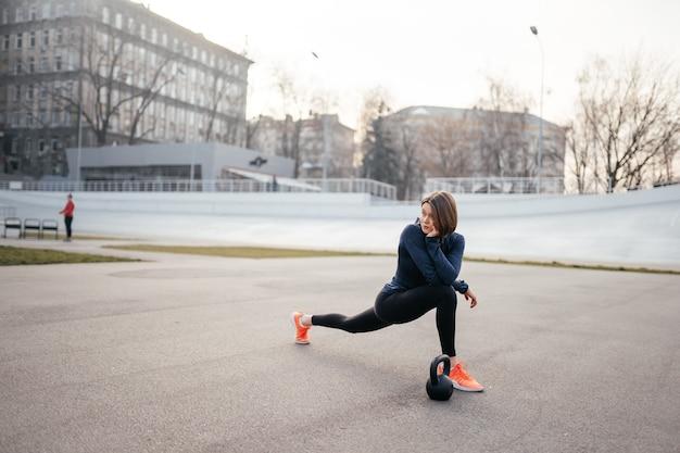 Volledig lengteschot van geschikte jonge vrouw die uitrekkende training doet. fitness model oefenen in de ochtend buitenshuis.