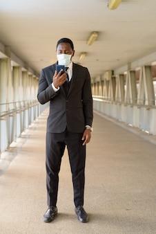 Volledig lichaam dat van afrikaanse zakenman met masker is ontsproten dat telefoon met behulp van bij de voetgangersbrug
