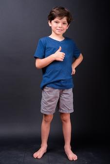 Volledig lichaam dat van gelukkige jonge knappe jongen is ontsproten die duimen opgeeft