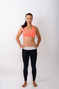 Volledig lichaam dat van jonge gelukkige aziatische vrouw is ontsproten die zich met handen op heupen bevindt klaar voor gymnastiek tegen witte ruimte