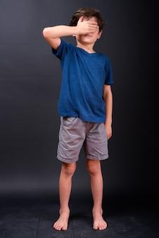 Volledig lichaam dat van jonge jongen is ontsproten die ogen bedekt die niet iets willen zien