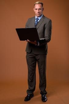 Volledig lichaam dat van zakenman is ontsproten die laptop computer met behulp van