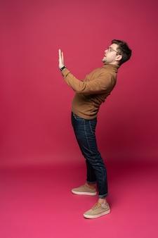 Volledig lichaam een jonge casual man die iets op roze achtergrond presenteert.