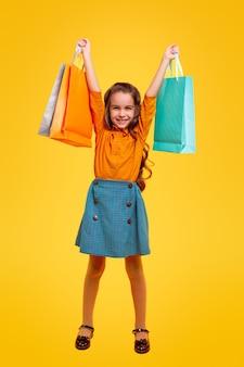 Volledig lichaam opgetogen klein meisje in stijlvolle vrijetijdskleding met een heleboel veelkleurige boodschappentassen, terwijl het mode- en winkelconcept vertegenwoordigt