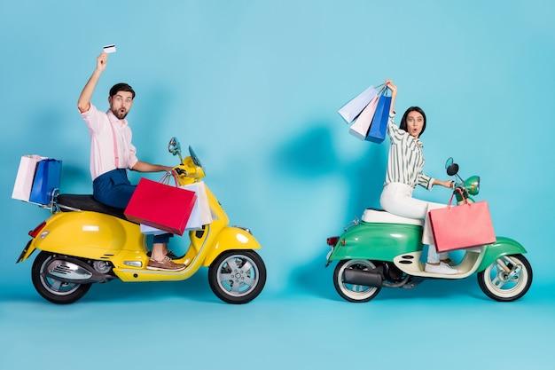 Volledig lichaam profiel zijfoto verrast twee mensen echtgenote man rijder chauffeur reizen helikopter onder de indruk winkel winkelcentrum kortingen houden pinpas tassen formalwear kleding geïsoleerd blauwe kleur muur