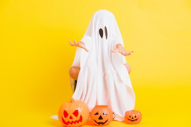 Volledig lichaam van een klein schattig kind met een wit gekleed spookkostuum