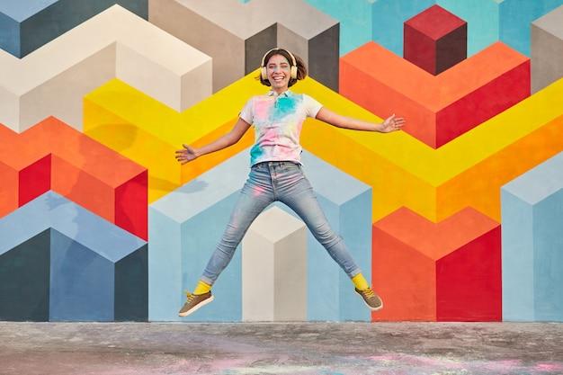 Volledig lichaams jong wijfje dat tegen kleurrijke muur springt