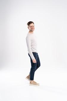 Volledig lichaamsbeeld van een glimlachende toevallige mens die zich op wit bevindt