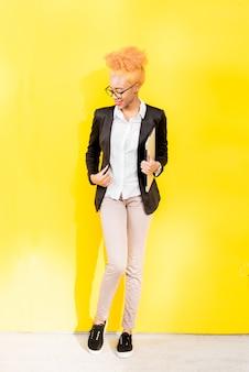 Volledig lichaamsportret van een afrikaanse zakenvrouw in een casual pak met laptop op de gele muurachtergrond