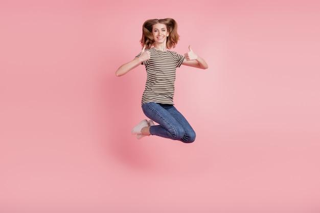 Volledig lichaamsportret van een jonge vrouw, een gelukkige positieve glimlach, laat een duim omhoog zien als een coole fijne sprong omhoog geïsoleerd over een roze kleurachtergrond
