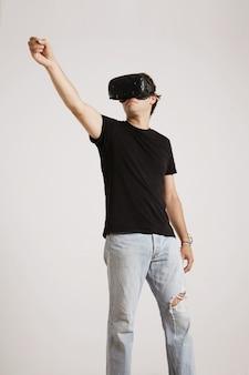 Volledig lichaamsportret van een man in gescheurde spijkerbroek en zwarte t-shirt zonder label met vr-headset die iets hoog houdt geïsoleerd op wit