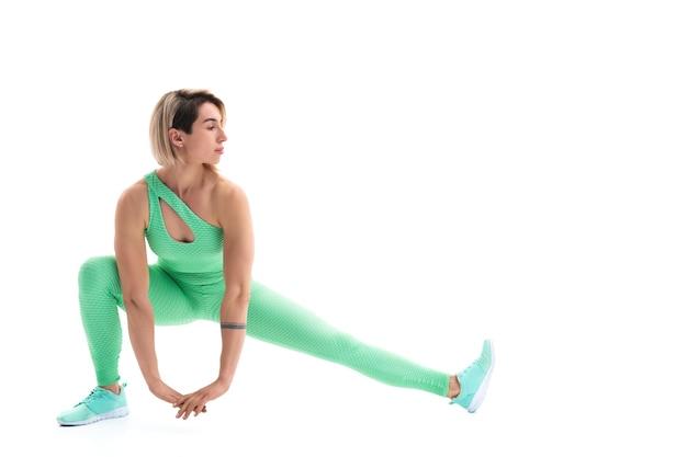 Volledig lichaamsportret van het jonge sportieve vrouw die zich uitstrekt