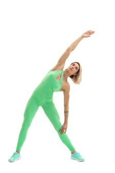 Volledig lichaamsportret van het jonge sportieve vrouw uitrekken zich vóór oefening