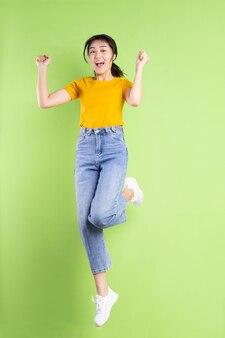 Volledig lichaamsportret van jong aziatisch meisje op groene muur