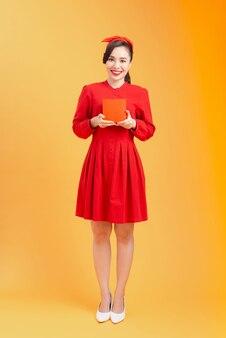 Volledig lichaamsportret van jonge aziatische vrouw met rode giftdoos. oranje achtergrond geïsoleerd.