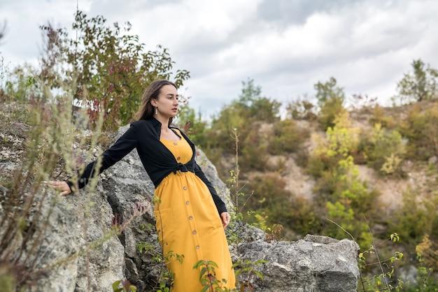 Volledig lichaamsportret van jonge vrouw dichtbij grote steen bij steengroeve, de zomerreizen. levensstijl