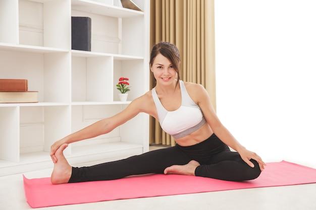 Volledig lichaamsportret van mooi sportief meisje dat been het uitrekken doet