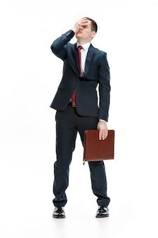 Volledig lichaamsportret van zakenman met omslag op witte muur